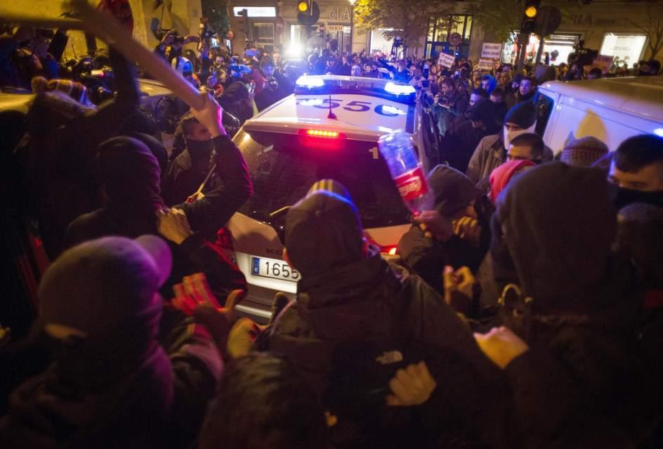 A golpes contra un coche de Policía. Un activista se dispone a golpear la luna de un coche de Policía en la calle San Sebastián de Madrid.