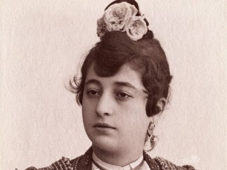 A female bullfighter, with flowers in her hair, wearing a matador's jacket. Photograph by Castillo, ca. 1900