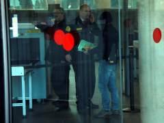 Un encapuchado, presumiblemente uno de los mossos imputados en el  'caso Raval', entra en la Ciudad de la Justicia de Barcelona.