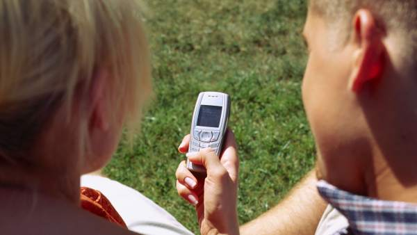 Dos personas envían un SMS con el móvil.