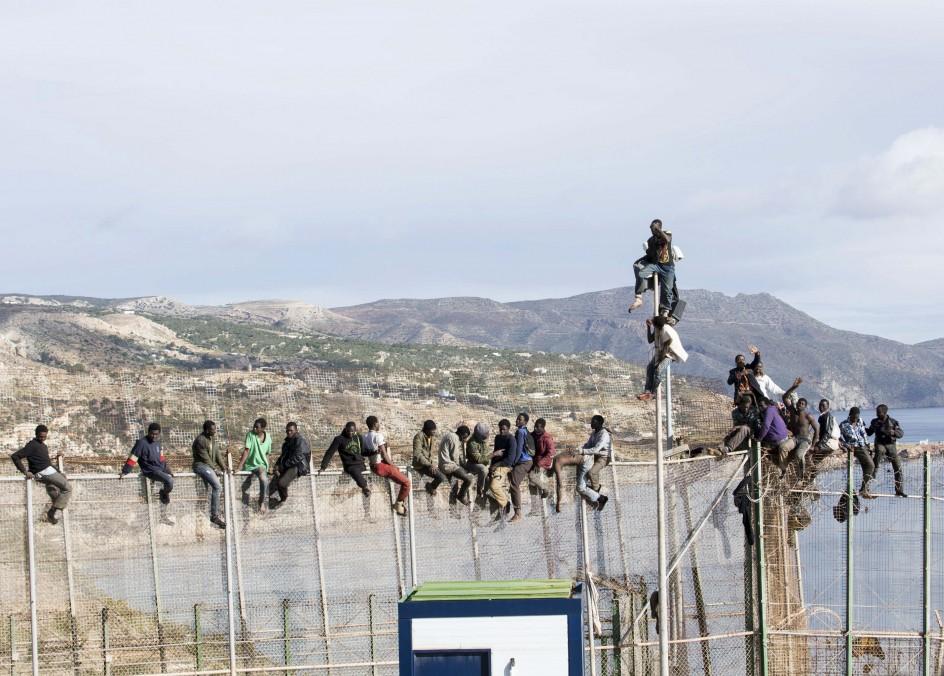 Encaramados en la valla de Melilla