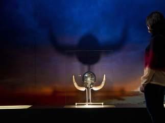 Una mujer observa una réplica de un casco vikingo.