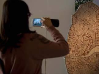 Una mujer hace una foto de una piedra sepulcral original vikinga.