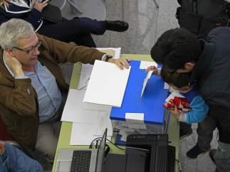 Un ni�o introduce el voto de su padre en una urna en las elecciones al Parlamento Europeo celebradas en Catalu�a.