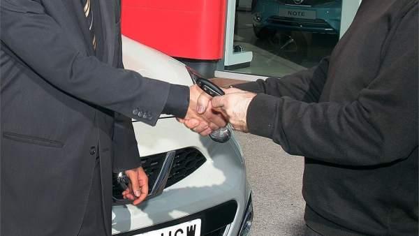 Un hombre adquiere un coche en un concesionario