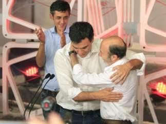 Rubalcaba abraza a Sánchez tras ganar las primarias del PSOE mientras Madina aplaude.