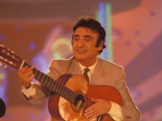 De traje y con su guitarra