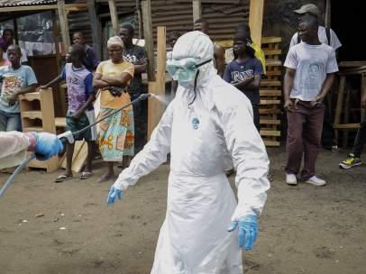 Desinfectan el traje a un miembro del personal médico que lucha contra el ébola