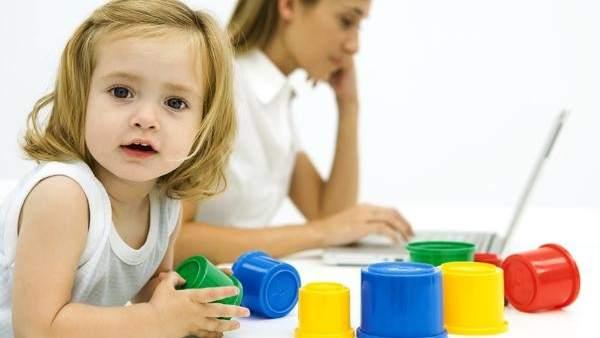 Madre con el ordenador mientras su hija juega