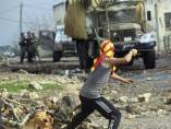 Un palestino lanza piedras a un cañón de agua del ejército israelí.