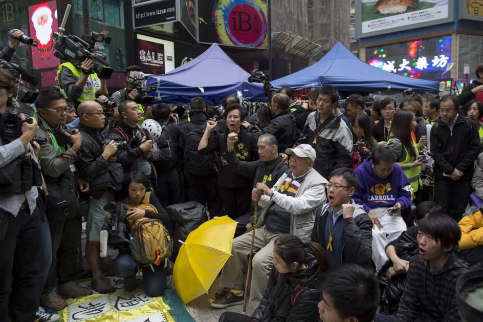 Desmantelan el campamento de Occupy Central . El último grupo de manifestantes grita consignas mientras la policía desmantela el último campamento protesta de Occupy Central, en el distrito comercial honkonguense de Causeway Bay, en China. La policía de Hong Kong disolvió hoy el último reducto de los asentamientos prodemocracia en la ciudad con la detención de 17 personas en un concurrido distrito comercial.