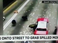 Personas recogiendo dinero perdido por un furgón de seguridad
