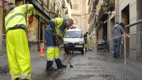 Un grupo de operarios retira la cera acumulada en la calle Marqués de Gerona.