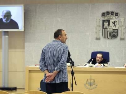 Los etarras Javier Ugarte Villar (d, de espaldas) y Jose Luis Erostegi Bidaguren (izda. por videoconferencia) durante el juicio.