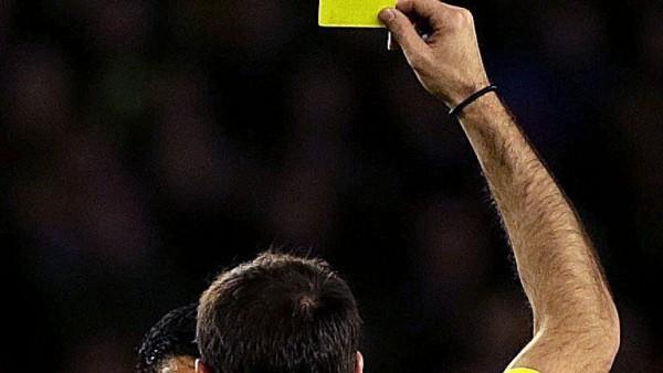 Un árbitro amonesta a un jugador