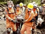 Los servicios de emergencia colombianos rescatan cuerpos entre los destrozos producidos por la avalancha.