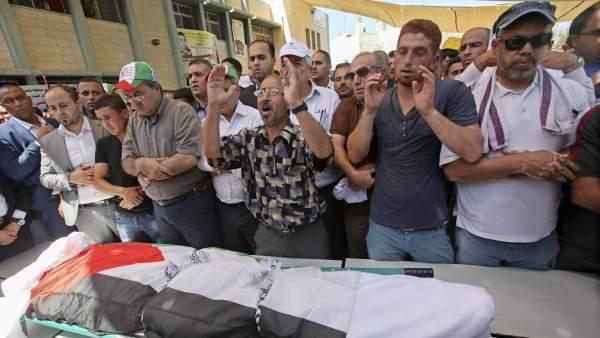 Familiares y allegados de la familia palestina rezan por el cuerpo de Saad Dawabsha durante su funeral.