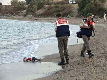 Un polic�a recoge el cad�ver de un ni�o en una playa de Turqu�a
