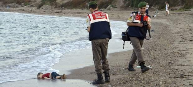 Un policía recoge el cadáver de un niño en una playa de Turquía