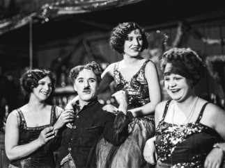 "Chaplin relaxes with the dance hall girls on the set of ""The Gold Rush"" (1925)"