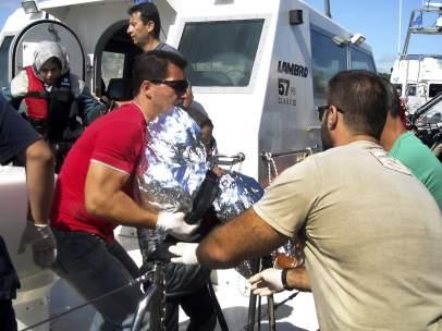 Oficiales de la Guardia Costera desembarcan a un niño inmigrante envuelto en una manta térmica en el puerto de Mytilini, en la isla de Lesbos (Grecia).