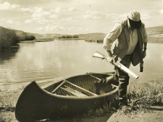 Ernest Hemingway stepping out of a canoe, Sun Valley, Idaho, October 1941