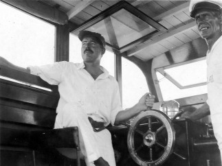 Ernest Hemingway at the wheel of his boat, Pilar, with Carlos Gutierrez, 1934