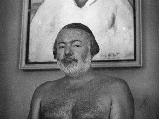 Photograph of Hemingway at the Finca Vigia, posing in front of Waldo Pierce's 1929 oil portrait, Kid Balzac, which depicts Hemingway, 1952