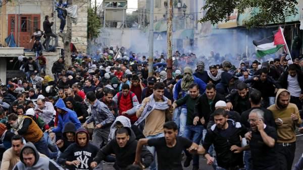 Cientos de palestinos corren tras el lanzamiento de granadas