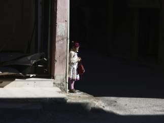 Una niña siria espera en la sombra de un edificio rebelde en Hamoria, en las afueras de Damasco