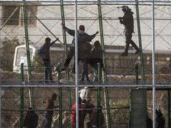 Ciudadanos subsaharianos en la valla que separa Melilla de Marruecos