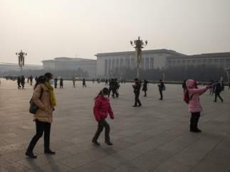 Los transeúntes que pasean por Tiananmen Square llevan mascarillas por los altos niveles de contaminación.