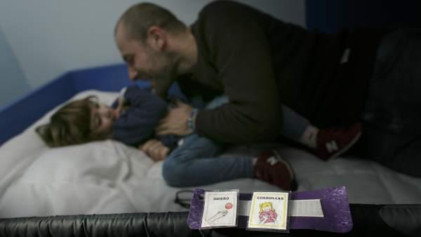 Ares, una niña con autismo, le pide cosquillas a su padre.