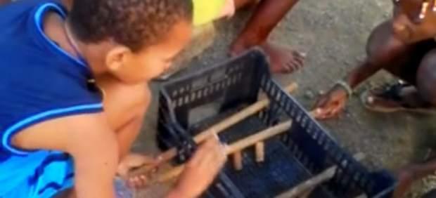 Unos niños jugando(divirtiendote) con un futbolín artesanal en Cabo Verde en Facebook