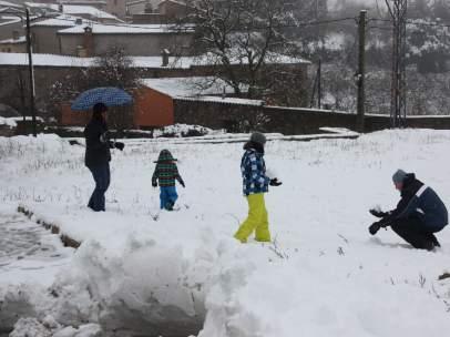 Plano general de una familia con dos niños jugando en la nieve.