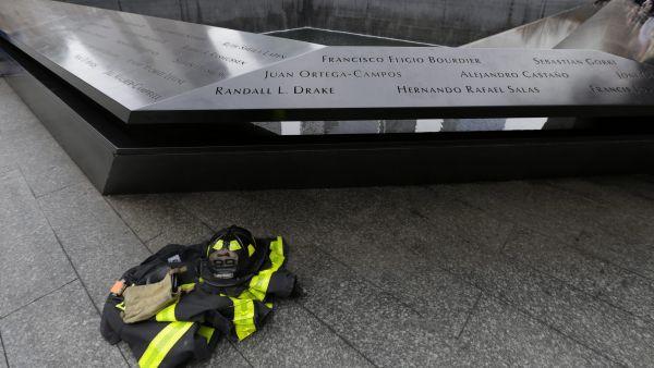 La equipo de un bombero reposa al lado del monumento en recuerdo de las víctimas del 11-S, situado en la plaza del World Trade Center de Nueva York.