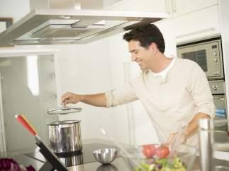 Un hombre cocina sobre una placa vitrocerámica