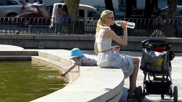 Una mujer bebe agua para refrescarse en Madrid
