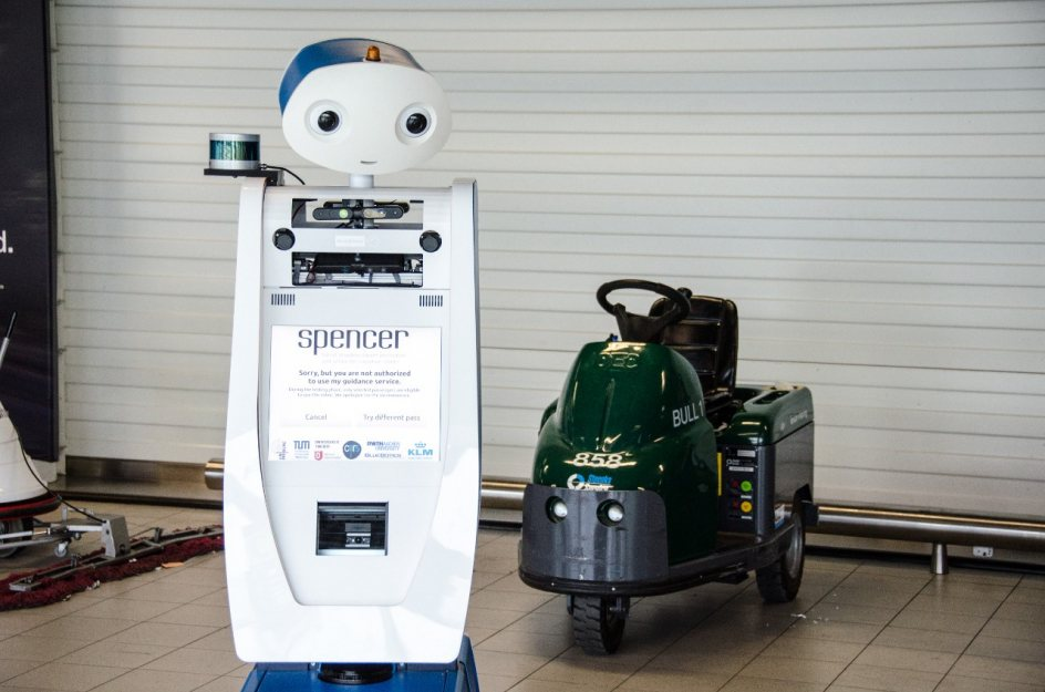 El robot Spencer junto a una máquina limpia suelos
