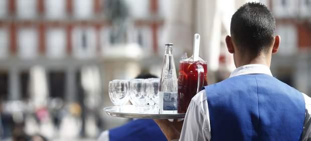 Un camarero sirve bebidas en una terraza