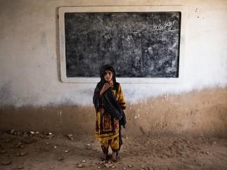 Malin Fezehai - Six year old Gul Bano stands in the ruins of her classroom in Haji Karfoor Jat, Thatta region, Sindh province, Pakistan, 2016
