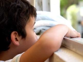 Niño mirando por la ventana.
