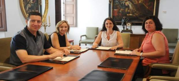 Gómez (centro) tras la firma del acuerdo