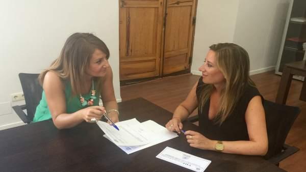 Pilar Palomares (i) revisa los vales-libros junto a la alcaldesa, Yolanda Reche.