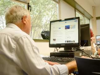 Un jubilado con un ordenador realizando gestiones.