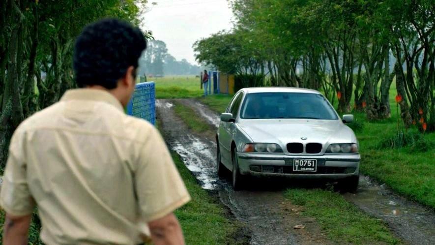 En esta escena del capítulo ocho de la primera temporada, una periodista llega a la finca de Pablo Escobar en un BMW Serie 5 E39. Coche que no fue fabricado hasta 1995, pero que en la serie, ambientada en los años 80, aparece.