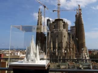 Una maqueta de la Sagrada Familia con las torres acabadas y, al fondo, el templo a día de hoy.