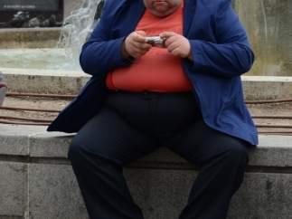 Una persona con obesidad sentada mirando su cámara de fotos.