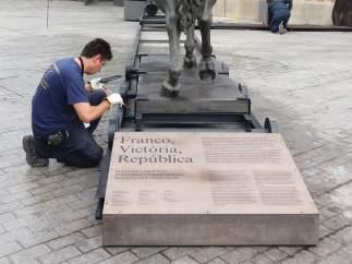 Un hombre anclando una estatua de Franco decapitado frente al Born CCM.
