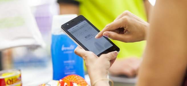 Una persona pagando con su teléfono móvil en un supermercado.